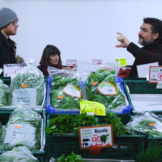 Koch Orhan Tançgil zeigt den Workshop Teilnehmern die Auswahl im türkischen Supermarkt.